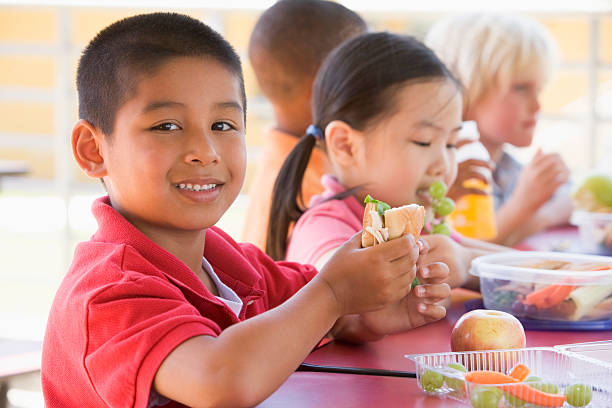 Picture of boy eating sandwich with children in cafeteria